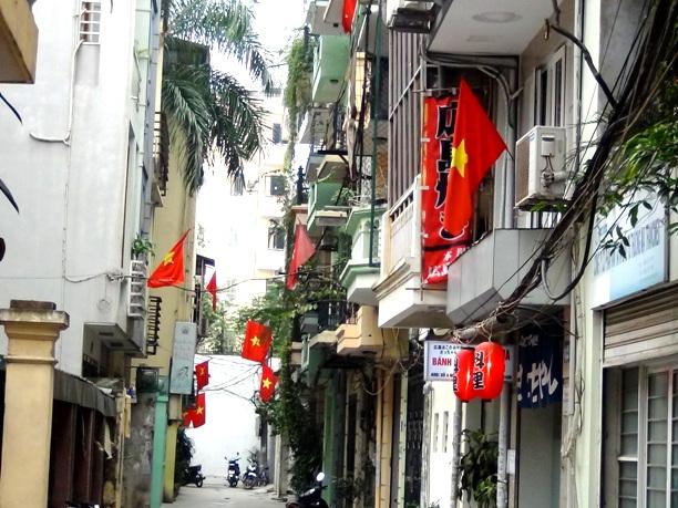 国民の祝日に必ず国旗を揚げるベトナムの人々