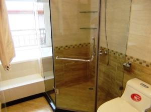 グラスシャワーの向こうに80リットルを確保できるバスタブがあります