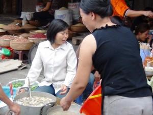 市場で食材をさばくおばさん達