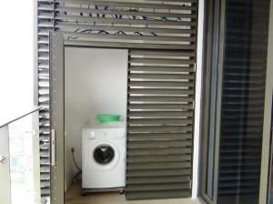 バルコニーにある洗濯機と物干しスペース