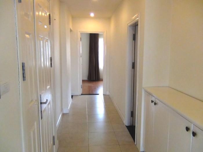 白がまぶしいリビングからベッドルームに通じる廊下スペース