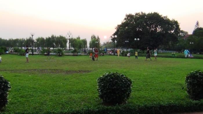 夕暮れ迫る緑地の公園で遊ぶ国際色豊かな子供たち
