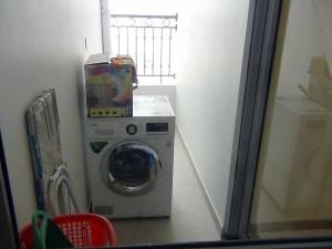 屋根のあるベランダに洗濯機が設置されています