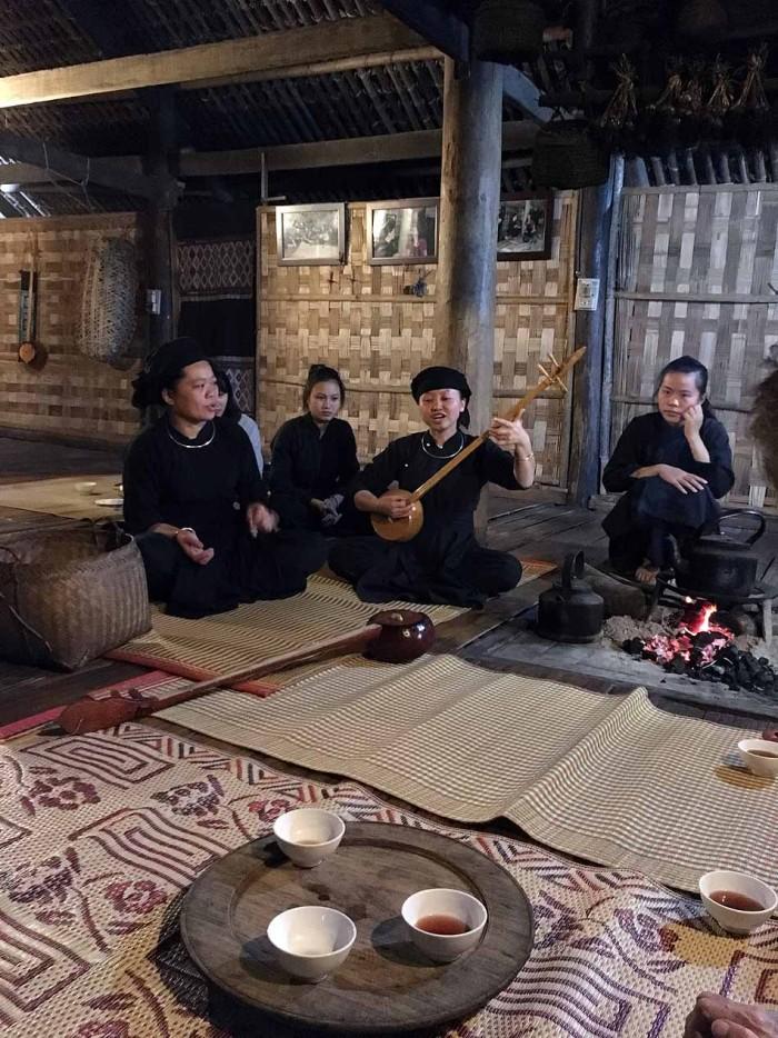 高床式の住居でお鍋をいただく前に、音楽を奏でてくれます